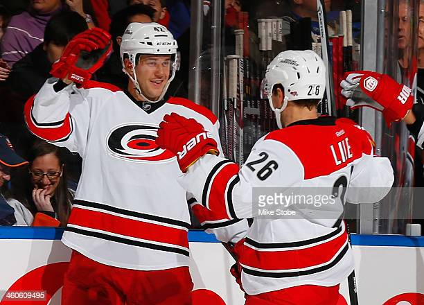 Brett Sutter of the Carolina Hurricanes is congratulated on his second period goal by teammate John-Michael Liles during the game against the New...