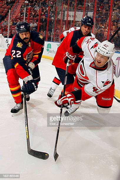 Brett Sutter of the Carolina Hurricanes skates for possession against George Parros and Stephen Weiss of the Florida Panthers at the BB&T Center on...