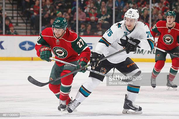 Brett Sutter of the Minnesota Wild and Freddie Hamilton of the San Jose Sharks skate to the puck during the game on January 6, 2015 at the Xcel...