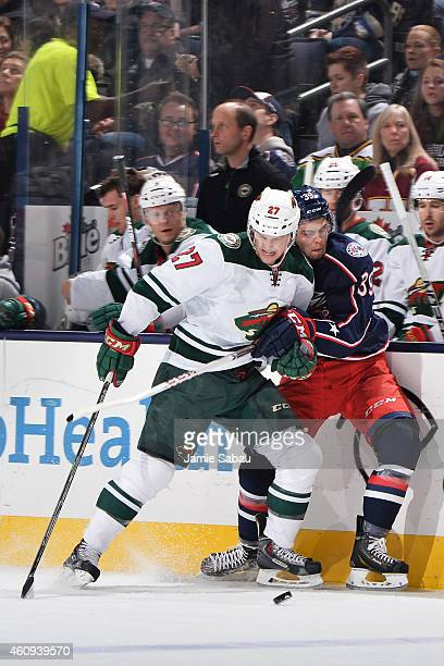 Brett Sutter of the Minnesota Wild and Michael Chaput of the Columbus Blue Jackets battle for a loose puck during the first period on December 31,...