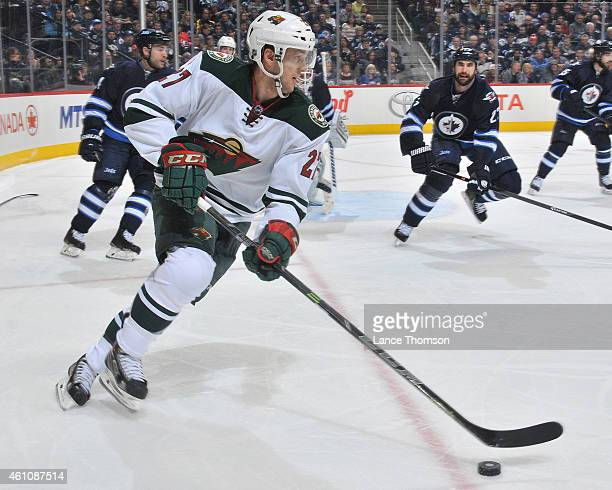 Brett Sutter of the Minnesota Wild plays the puck as Jay Harrison of the Winnipeg Jets defends during third period action on December 29, 2014 at the...