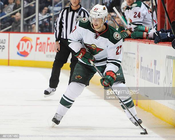 Brett Sutter of the Minnesota Wild plays the puck up the ice during third period action against the Winnipeg Jets on December 29, 2014 at the MTS...
