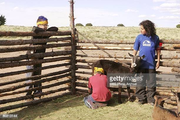 Brett watches Colton milking the goat that Guylan holds still in KID NATION on the CBS Television Network