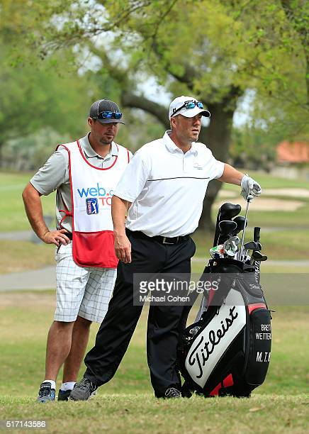 Brett Wetterich pulls a club from his golf bag as his caddie former Major League Baseball pitcher Josh Beckett looks on during the first round of the...