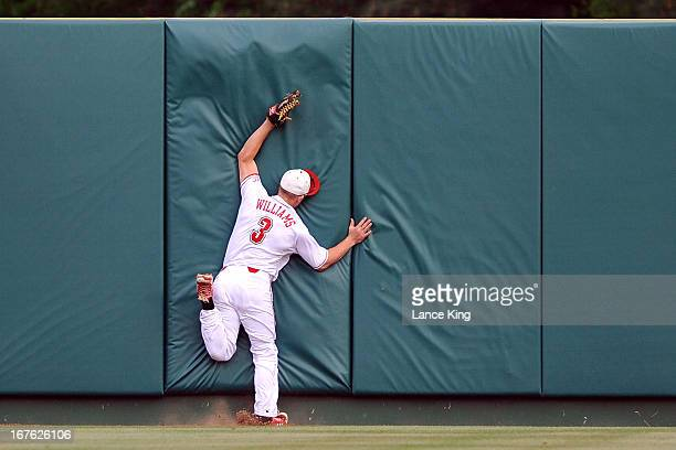Brett Williams of the North Carolina State Wolfpack runs into the center field wall during a game against the North Carolina Tar Heels at Doak Field...