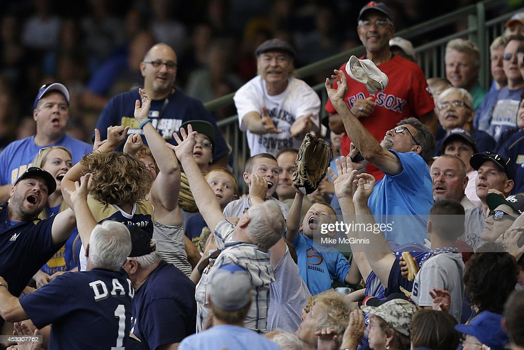 A Brewer fan catches a foul ball in a hat during the seventh inning between the San Francisco Giants and the Milwaukee Brewers at Miller Park on August 07, 2014 in Milwaukee, Wisconsin.