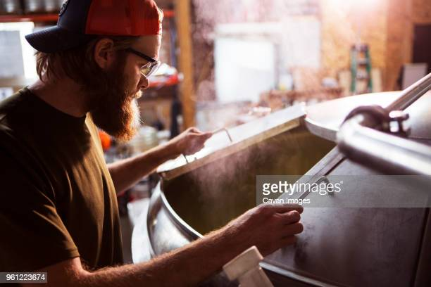 brewer looking in machinery at brewery - 醸造所 ストックフォトと画像