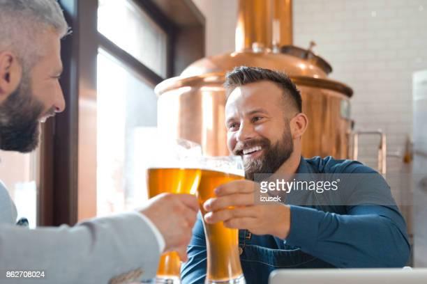 Brauerei Meister Toasten mit Bierglas mit seinem Freund