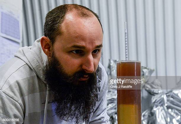 A brewer measures beer density to ensure sugar has turned into alcohol at inner city craft beer makers Brixton Brewery on December 8 2015 in London...