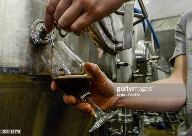 Brewer Sam Jory takes a sample of Windrush Stout from a fermenting vessel at inner city craft beer makers Brixton Brewery on December 8 2015 in...