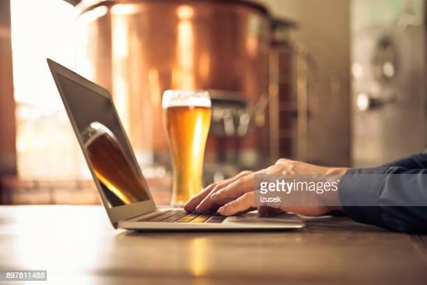 Brauer mit Laptop in der Mikro-Brauerei
