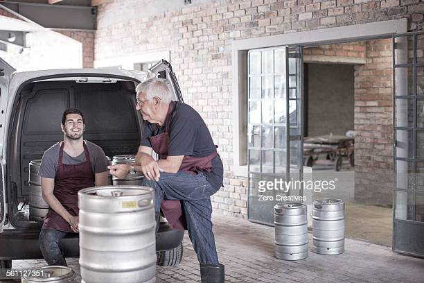 Brewers loading kegs into back of van