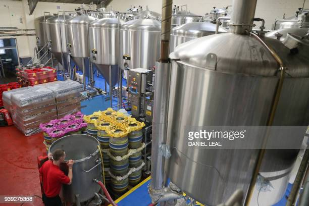 Brewery operator Steve looks inside a container being filled with water next to beer vessels at the Windsor Eton Brewery in Windsor England on March...