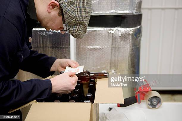 Brewery technician putting labels on beer bottles