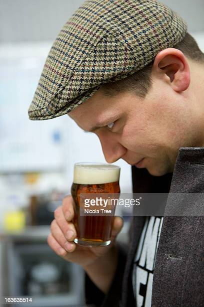 A brewery technician smelling and tasting beer.