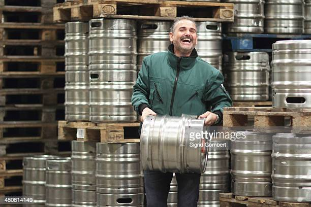 Brewery worker carrying barrel