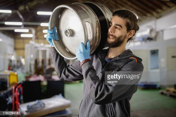 brewery worker carrying keg - brewery stock pictures, royalty-free photos & images