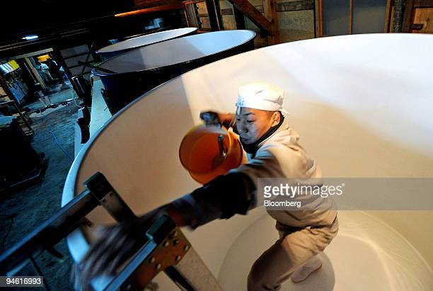 Brewery worker climbs out of a 4000 liter tank used in the fermentation process to make sake after sterilizing the tank at the Tamagawa Sake Brewery...
