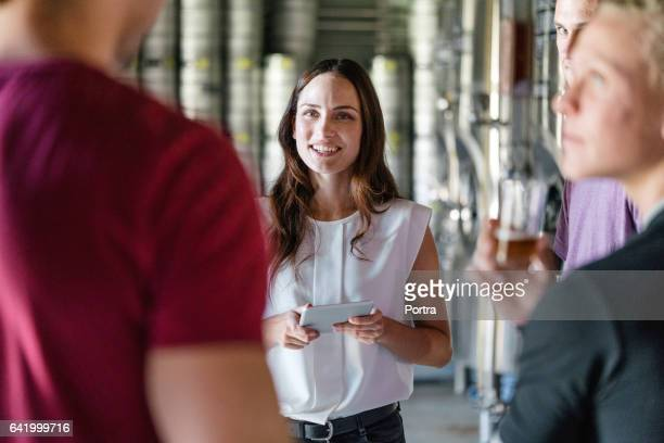 Brewery worker holding tablet PC in meeting