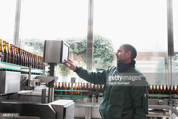brewery worker operating bottling machine - sigrid gombert stock pictures, royalty-free photos & images