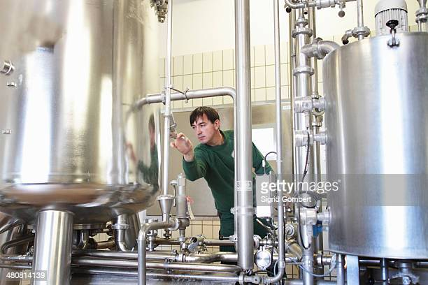 brewery worker operating machine - sigrid gombert stock pictures, royalty-free photos & images