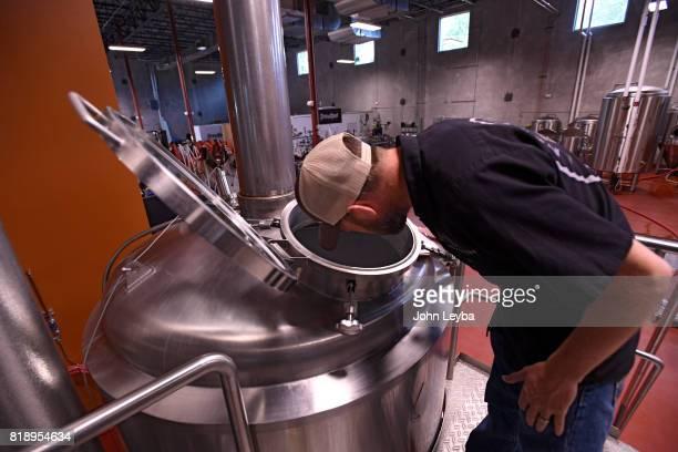 Brewmaster Josh Robbins of New Terrain Brewing checks the vats where he brews a Colorado IPA on July 19 2017 at New Terrain Brewing in Golden Josh...