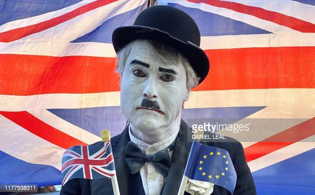 Brexit activist dressed as the late English comic actor Charlie Chaplin holds a Union and an EU flag as he protests outside the Houses of Parliament...