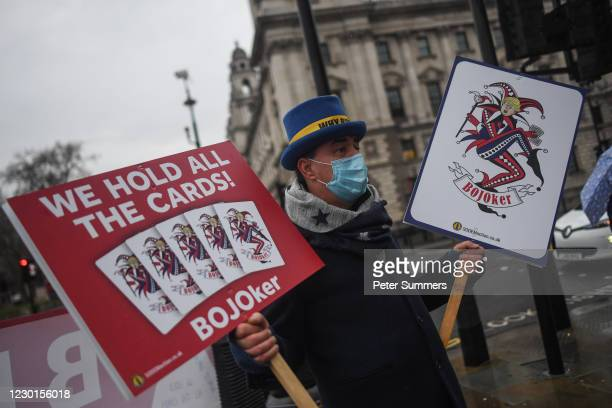 Brexit activist Steve Bray holds signs reading 'We Hold All The Cards' and depicting British PM Boris Johnson as a joker at an anti-Brexit protest...