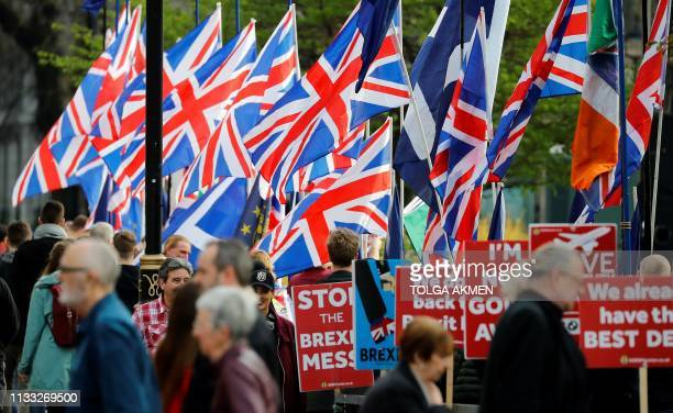 Brexit activists flie Union flags as antiBrexit activists hold placards as they demonstrate near the Houses of Parliament in Westminster London on...