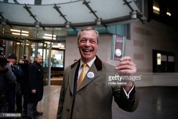 Brexit Party leader and former MEP, Nigel Farage holds up commemorative 50p Brexit coin as he arrives to appear on the Andrew Marr Show at BBC...