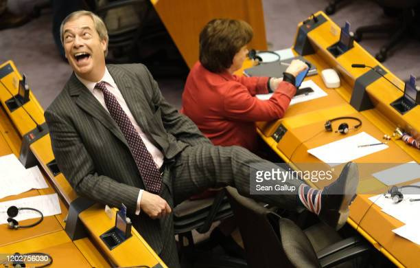 Brexit Party leader and member of the European Parliament Nigel Farage shows off his socks at a session of the European Parliament in which it is to...