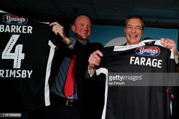 Brexit Party leader Nigel Farage and Chris Barker Parliamentary candidate for Grimsby hold up a Grimsby Town Football Club shirts with their names on...