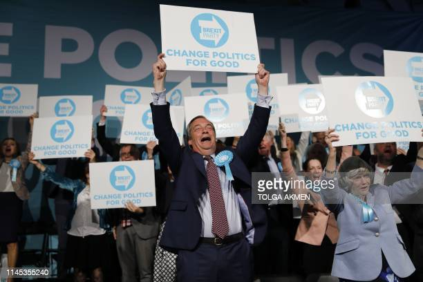 Brexit Party leader Nigel Farage holds up a placard at the end of a European Parliament election campaign rally at Olympia London west London on May...