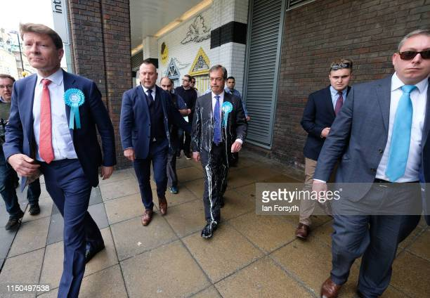 Brexit Party leader Nigel Farage is escorted to a car after having what is thought to be milkshake thrown over him as he visits Northumberland Street...