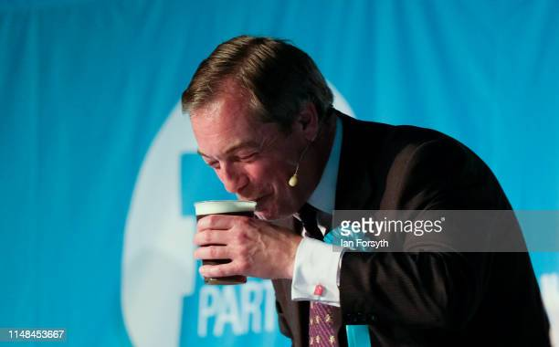 Brexit Party leader Nigel Farage is handed a drink after his speech during a Brexit Party campaign at Rainton Meadows Arena in Houghton Le Spring on...