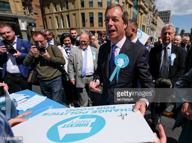 Brexit Party leader Nigel Farage signs party placards for supporters as he visits Northumberland Street in Newcastle Upon Tyne during a whistle stop...