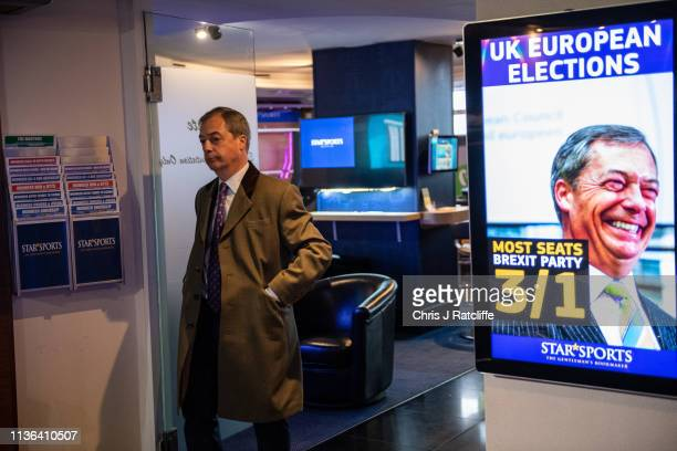 Brexit Party leader Nigel Farage walks past a screen in a book makers displaying odds for the UK European Elections after he placed a £1000 bet on...
