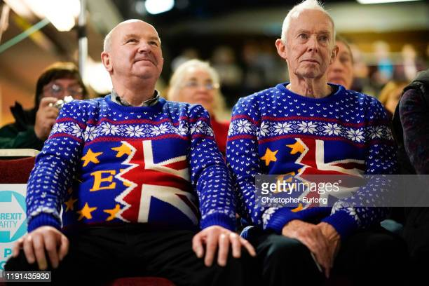 Brexit party supporters Barry Clarkson and Alastair Sutcliffe wear their Brexit Christmas jumpers as they listen to Brexit party leader Nigel Farage...