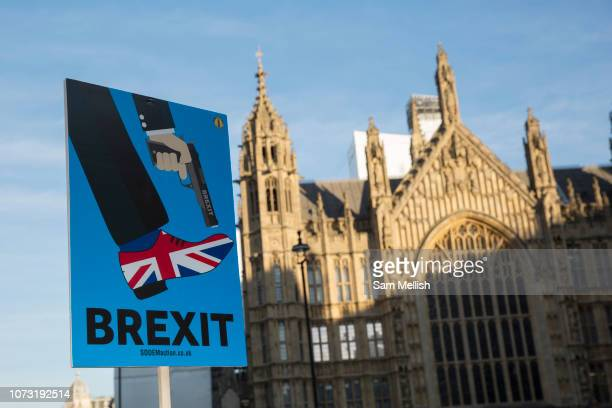 A Brexit placard outside Houses of Parliament showing a smartly dressed person holding a gun to a shoe in the Union Jack colours on the 13th December...