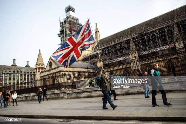 Brexit protester demonstrates with the Union Flag outside the Houses of Parliament in Westminster on January 29 2019 in London England MPs debate the...