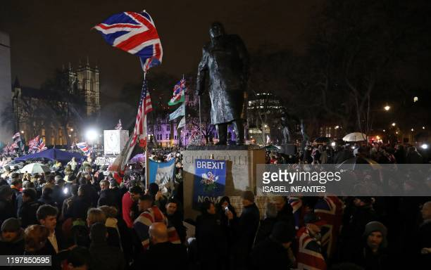 Brexit supporter wave Union flags as they wait near a statue of British wartime Prime Minister Winston Churchill for the festivities to begin in...