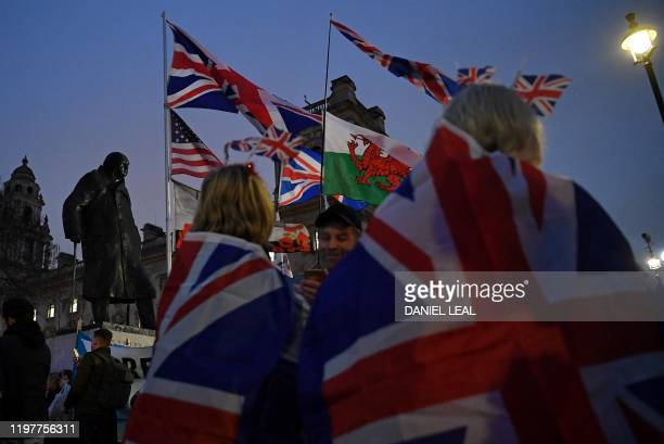 Brexit supporters carry Union flags and a Welsh flag as they gather in Parliament Square in central London on January 31 2020 on the day that the UK...