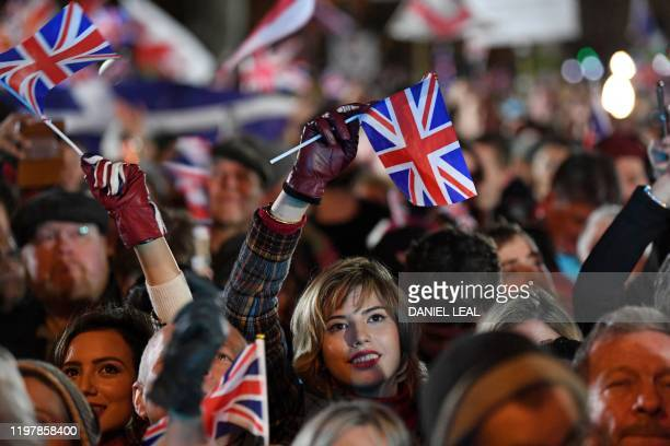 TOPSHOT Brexit supporters wave Union flags as the time nears 11 O'Clock in Parliament Square venue for the Leave Means Leave Brexit Celebration in...