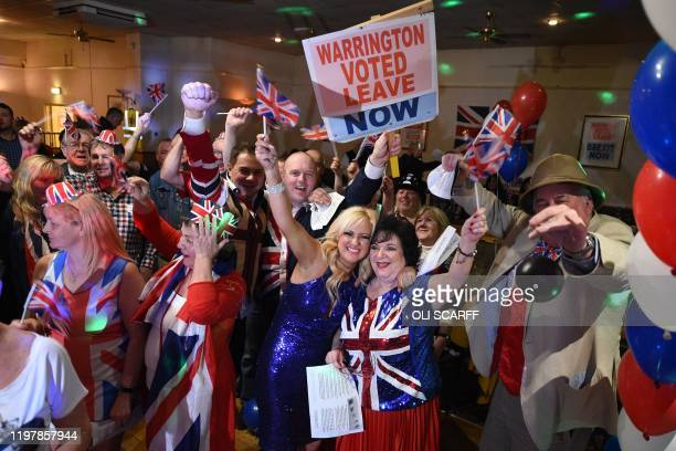 Brexit supporters wave Union flags as the time passes 11 O'Clock at a Brexit Celebration party at Woolston Social Club in Warrington north west...