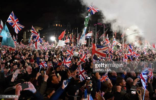 TOPSHOT Brexit supporters wave Union flags as the time reaches 11 O'Clock in Parliament Square venue for the Leave Means Leave Brexit Celebration in...