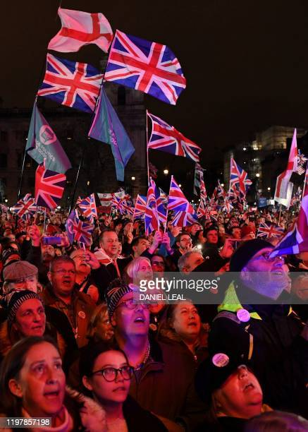 Brexit supporters wave Union flags as they watch the big screen in Parliament Square venue for the Leave Means Leave Brexit Celebration party in...