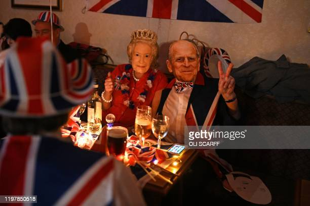 Brexit supporters wearing masks of Britain's Queen Elizabeth II and Britain's Prince Philip, Duke of Edinburgh pose for a photograph during a Brexit...