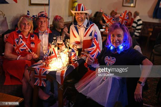 Brexit supporters wearing Union flag hats and holding mini-Union flags pose for a photograph during a Brexit Celebration party at Woolston Social...