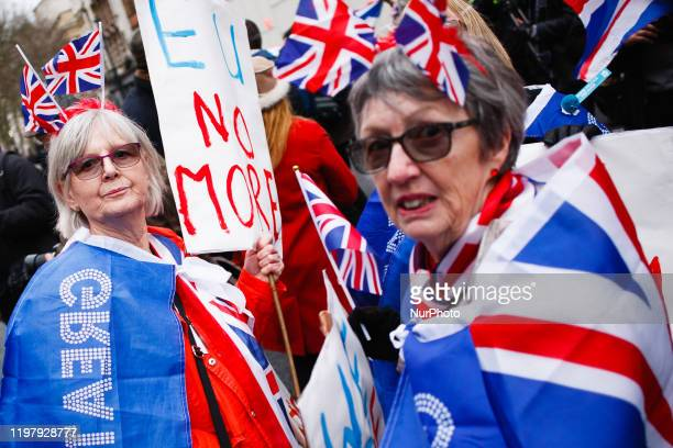 Brexit supporters wearing Union Jack flags celebrate on Parliament Street in London, England, on January 31, 2020. Britain's exit from the European...