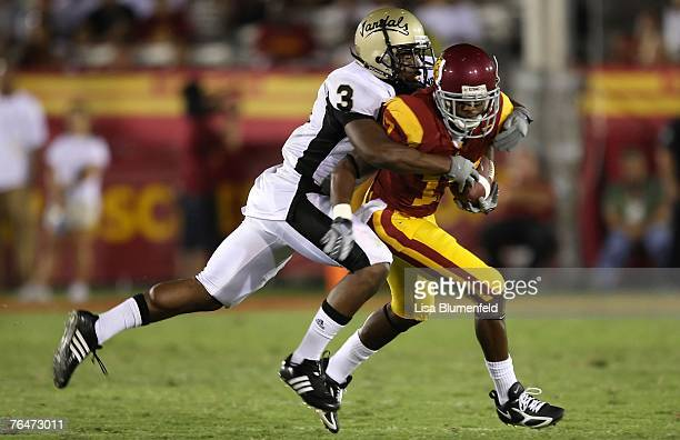 Breyon Williams of the University of Idaho Vandals tackles Travon Patterson of the USC Trojans at the Los Angeles Memorial Coliseum on September 1...